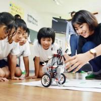 プログラム通りにロボットが動くか見守るロボギャルズメンバーと児童=13日、龍瀬小