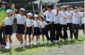 児童生徒らと八月踊りを練習する鹿大の学生=4日、奄美市名瀬の芦花部小中学校