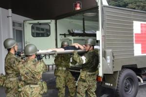 患者を他の医療機関へ搬送する訓練に当たる奄美陸上自衛隊の衛生隊員=12日、県立大島病院