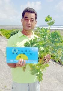 主原料のボタンボウフウと受賞製品を手にする高木工場長=14日、喜界町阿伝