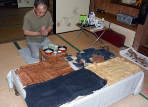 自宅に飾ったノロ装束「シバサシギン」に手を合わせる住民=12日、宇検村阿室