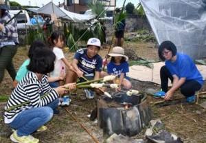 岳に巻き付けたパン生地を焼き上げる子どもたち=29日、徳之島町手々