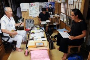 山下幸秀さん(左)の「えらぶの子守唄」に聞き入るレンゴさん(右)=8月11日、和泊町