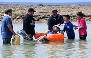 徳之島初のビーチ用車いすに乗り、海水浴を楽しむ障がい者と保護者ら=14日、伊仙町伊仙