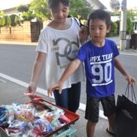 住民が準備したお菓子を集める子どもたち=14日、与論町