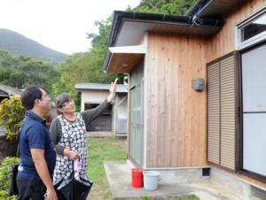 改修後の住宅を確認する町の職員(手前)と薩川集落の里ゆかり区長=19日、瀬戸内町加計呂麻島