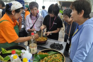 地元住民に教わりながら、郷土料理作りに挑戦するシニア自然大学校の講座生ら=7日、知名町の農村婦人センター