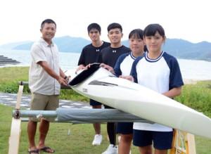 寄贈されたカヌーのそばで笑顔を見せる大島北高カヌー部メンバーと白畑さん(左)=7日、赤木名海岸