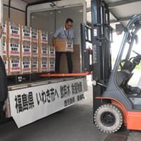 台風19号で被災した福島県いわき市へ送る飲料水の積み込み作業=21日、奄美市住用町