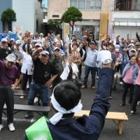 出陣式で頑張ろう三唱する支持者ら=20日午前9時40分ごろ、奄美市名瀬