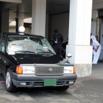 摘出された臓器を乗せ、奄美空港に向かうタクシーと、見送る病院スタッフ=22日、奄美市名瀬の県立大島病院