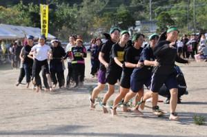 チームの団結力を発揮したむかで競走=6日、奄美市の住用総合グラウンド
