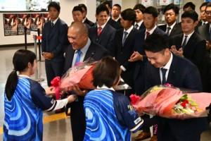 花束を受け取る(左から)アレックス・ラミレス監督、佐野恵太選手=31日、奄美市笠利町の奄美空港