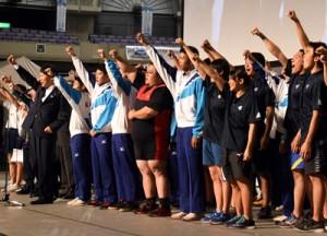 大会成功と選手の活躍へ気勢を上げた式典参加者(上)と、奄美市の相撲競技紹介ブース=20日、鹿児島市
