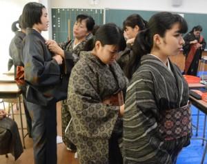 大島紬の着付けを体験する奄美高校の生徒ら=23日、奄美市名瀬