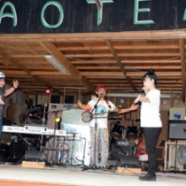 青テンライブでダンサーとともに大島エレジーを披露するタナカアツシさん(中央)=13日、龍郷町屋入