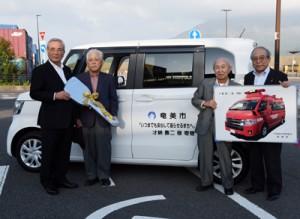 奄美市へ車両を寄贈した才納さん(左から2人目)=4日、鹿児島市