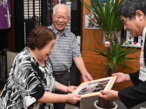 金婚式の記念写真を受け取る福山政雄さん(中央)と幸子さん(左)=15日、奄美市住用町