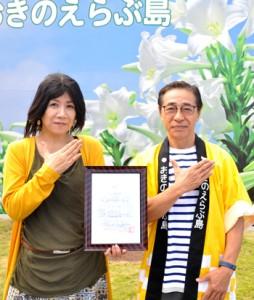 おきのえらぶ島観光協会の前登志朗会長から、観光親善大使の委嘱を受けた別府さん(左)=15日、和泊町