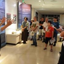 高梨修館長(左)の解説に聞き入るツアー参加者=8日、奄美市名瀬長浜町の奄美博物館