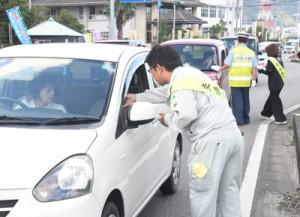 シートベルトの全席着用を呼び掛けたキャンペーン=4日、龍郷町瀬留の国道