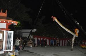 左に建っている社殿の屋根を飛び越えそうなほど高く宙を舞う大蛇=14日、知名町上平川