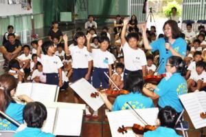 宇検村の集合学習で奄美オーケストラの演奏を楽しむ児童ら=17日、宇検村の田検小学校体育館