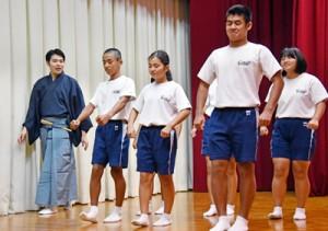 講師の指導を受けて、すり足に挑戦する生徒たち=16日、大和村の大和中体育館