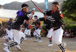 紙吹雪が舞う中、奉納された伝統の棒踊り=7日、瀬戸内町実久