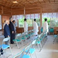 高千穂神社で行われた奉祝当日祭で、皇居の方角に向かい国歌を斉唱する参拝者たち=22日、奄美市名瀬