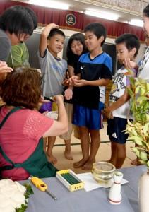 月を拝む伝統行事「カンサマオガミ」の一部、水にふやかした米を頭に付けてから食べる手順を体験する児童=14日、宇検村生勝