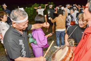 踊りの輪をつくる住民=25日、龍郷町中戸口