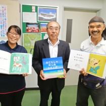 教育委員会を訪れ、町岡教育長(中央)に絵本の制作を報告した原田さん(右)と山田さん=10月30日、与論町