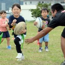 タグラグビーを楽しむ参加児童=30日、奄美市名瀬長浜町