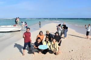 沖合に出現した百合ケ浜で記念写真に納まるFAMトリップの参加者たち=17日、与論島