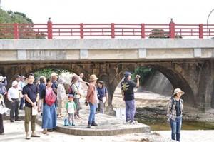 川底に下りて南洲橋を見学する、まち歩きの参加者=4日、和泊町