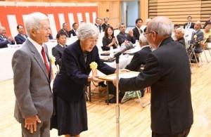 森田町長から祝い状を受け取る金婚夫婦=18日、天城町防災センター