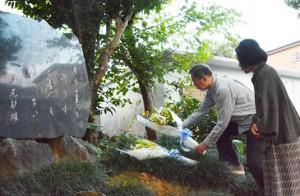 文学碑に献花する島尾伸三さん(奥)ら=12日、奄美市名瀬
