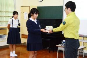大和小学校であった「希少野生動植物保護に向けた普及啓発トイレットペーパー」と「世界遺産学習漫画」の贈呈式=22日、大和村
