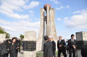 平和の塔へ献花後、石碑に刻まれた、親族や知人の名前を探す参列者ら=15日、知名町
