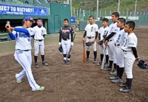 中学生にバッティングを指導する百瀬内野手(左)=9日、名瀬運動公園市民球場