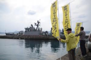 ミサイル艇しらたかに向かい、抗議ののぼりを立てる市民団体=20日、瀬戸内町古仁屋