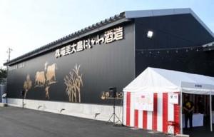 ㈱奄美大島にしかわ酒造の観光型新工場(上)と完成を祝って行われたテープカット=10日、徳之島町白井