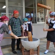 地域住民と共に餅つきをする大城小の児童=1日、和泊町