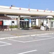 開港50周年の節目を迎えた沖永良部空港(上)と、空港に到着した利用客に記念品を配る関係者=和泊町