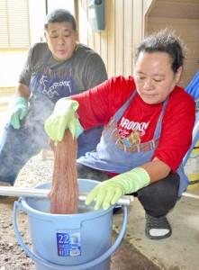 テーチ木を使い草木染の技法を学ぶクドゥボルさん(右)と夫の三浦さん=4日、大和村国直
