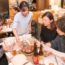 リュウキュウイノシシの加工食品を賞味する参加者=東京日本橋の離島キッチン