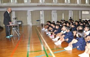 創立記念集会で、森田さん(左)から学校の歴史について話を聞く国頭小の児童=2日、和泊町の同校