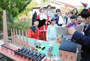 模型を見ながら、白糖工場の構造について学ぶ参加者ら=14日、瀬戸内町久慈