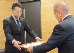 要田教育長から表彰状を受け取る諏訪会長(左)=6日、奄美市名瀬